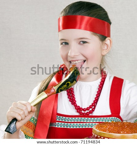 girl licks a wooden spoon with red caviar - stock photo