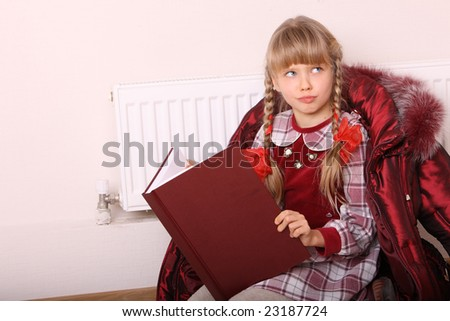 Girl lie near radiator with book. Cold crisis. - stock photo