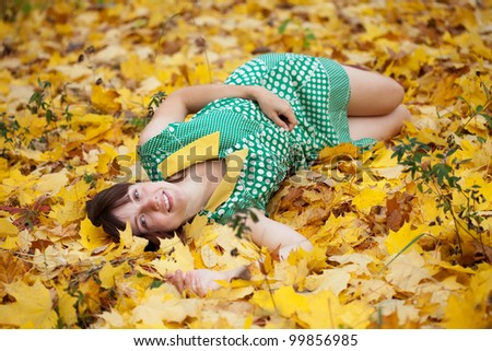 girl lies in maple leaves at autumn park - stock photo