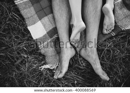Girl lies on guy on a picnic plaid. Foot plexus Legs closeup. Black and white - stock photo