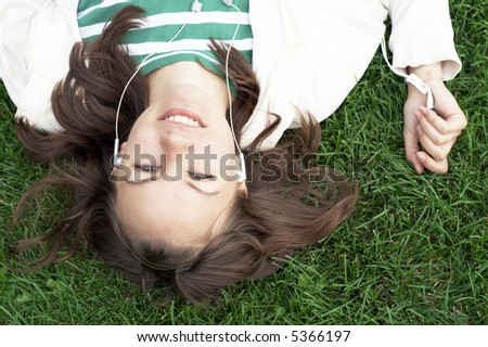 girl lies with mp3 player on the grass - stock photo