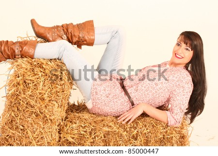 Girl lies with Western fashion on several straw bale /Country Girl