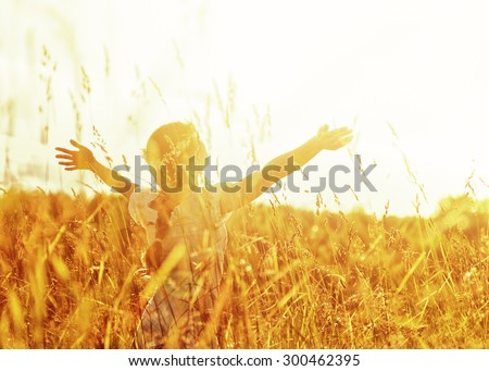 Girl lifting her hands up in the air to the sun. - stock photo