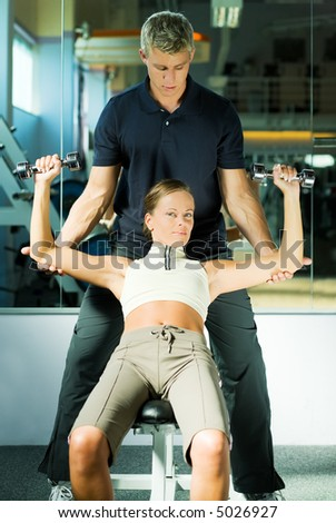 Girl lifting two dumb-bells, assisted by her personal trainer - stock photo