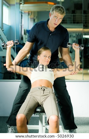 Girl lifting two dumb-bells, assisted by her personal trainer, both looking into the camera - stock photo