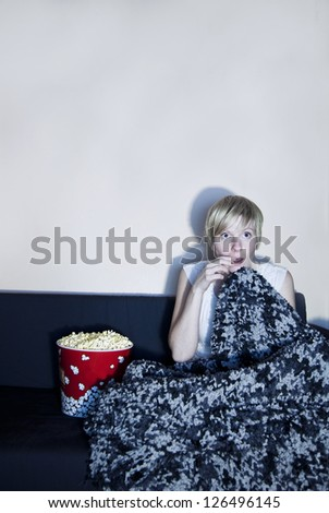 Girl listen to horror or suspense movie alone. Wrapped in a comfortable blanket, she is afraid of something happening and eating a huge popcorn. - stock photo
