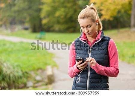 Girl listening music during training in park - stock photo