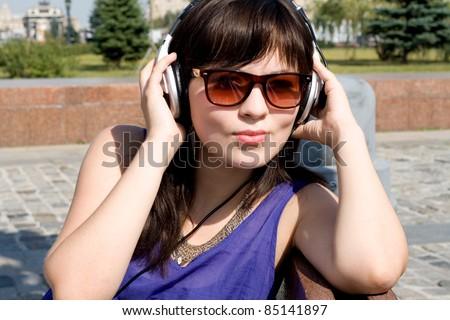 Girl listening music in headphones - stock photo