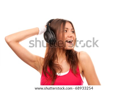 Girl listening music in headphones singing, smiling and holding her hand towards black headphones in pink top isolated on a white background - stock photo