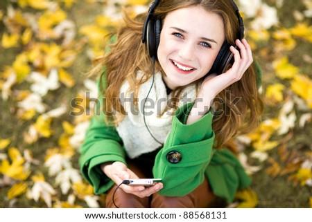 Girl listening music outdoors - stock photo