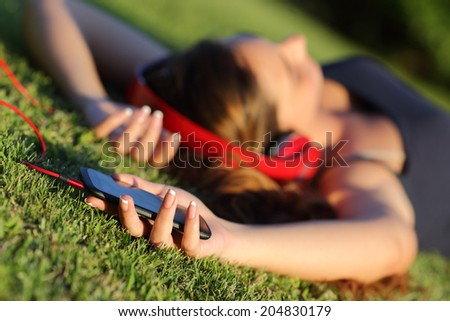 Girl listening music with headphones and holding a smart phone lying on the green grass in a park - stock photo
