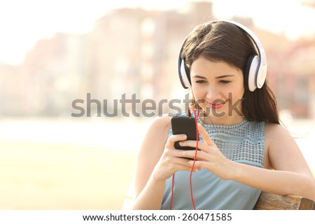 Girl listening music with headphones from a smart phone sitting in a bench in a park - stock photo