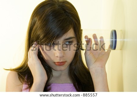 Girl listening through glass on wall eavesdropping on conversation. - stock photo