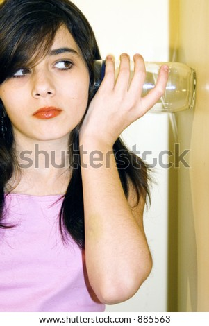 Girl listening through the wall, eavesdropping on conversation. - stock photo