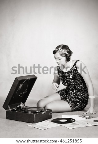 Girl listening to gramophone records. Vintage