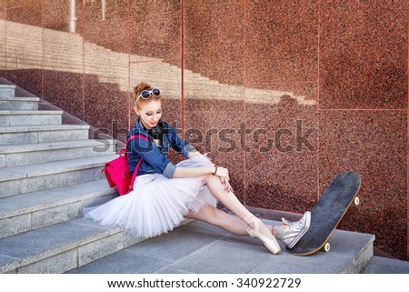 Girl listening to music on headphones. Funny hipster ballerina sits on the steps. A girl wearing a tutu, ballet shoes and sneakers, sunglasses. The girl is sitting on a skateboard. Youth fashion. - stock photo