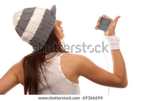 Girl listening to music on mp3 player in white headphones wearing hip-hop style hat and dance top isolated on white background - stock photo