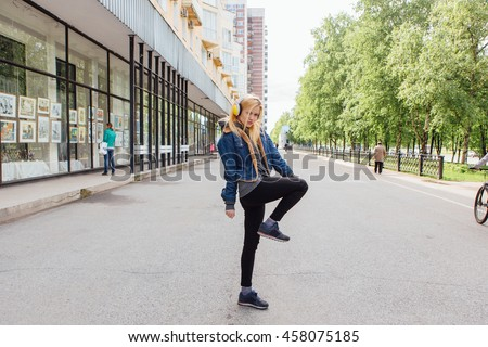 Girl listening to music streaming with headphones and dancing on the street.