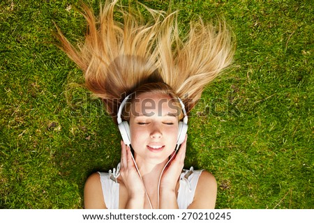 Girl listening to music streaming with headphones in summer on a meadow - stock photo