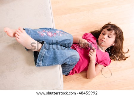 Girl listening to music while  laying on the floor