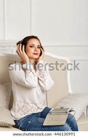 Girl listening to music while sitting on the couch. Girl with headphones holding a tablet computer. Girl enjoy your favorite tunes. Holiday home.