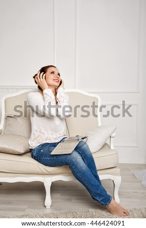 Girl listening to music while sitting on the couch. Girl with headphones holding a tablet computer. She enjoys the beautiful melody. Holiday home. - stock photo