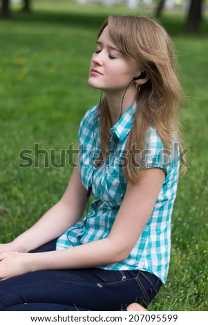 Girl listening to music with headphones while sitting on the grass - stock photo