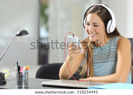Girl listening to the music with a smartphone and headphones in her desktop at home - stock photo