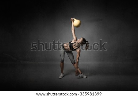 girl looking a kettlebell, textured background - stock photo