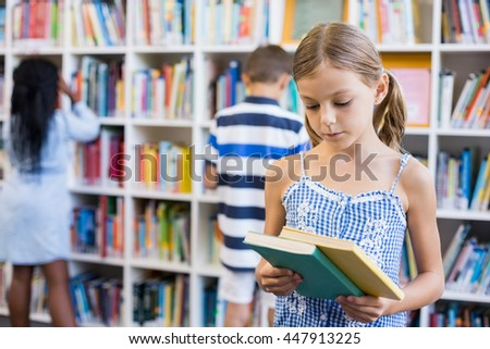 Girl looking at a book in library at school