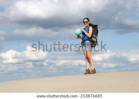 girl looking at a globe where they will travel - stock photo