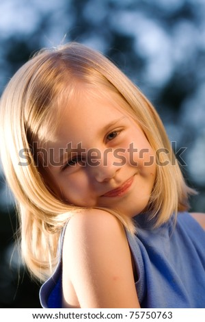 Girl looking at camera with blue natural background - stock photo