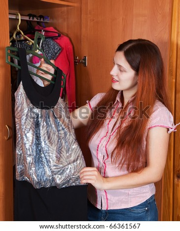 Girl looking at clothes in a closet - stock photo
