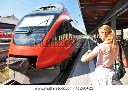 Girl looking at her watch at the train station - stock photo