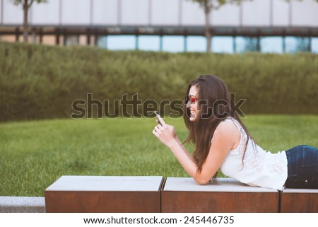 girl looking at phone smiling in park - stock photo