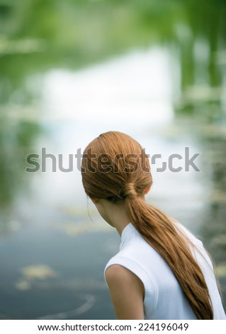 Girl looking at pond, rear view - stock photo