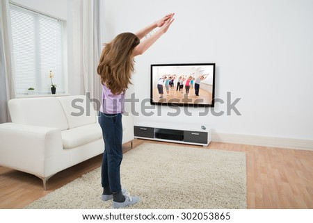 Girl Looking At Television While Doing Exercise At Home