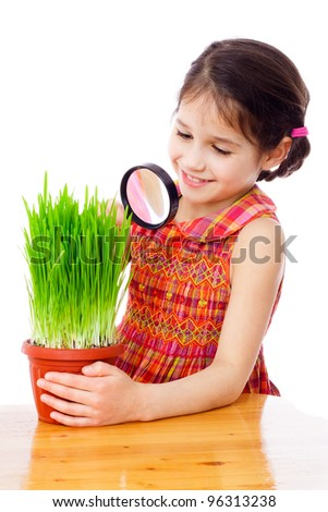Girl looking at the grass through a magnifying glass on the desk, isolated on white - stock photo