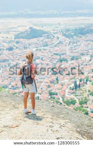 Girl looking at the town of Kalambaka bird's eye view. Meteora, Greece. Vertical view - stock photo