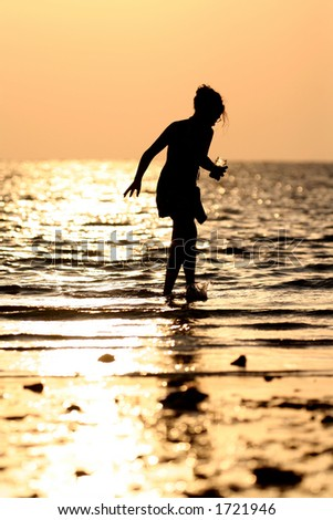 Girl looking for shells at sunset
