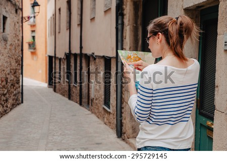 Girl looking for the road and looking at a map - stock photo