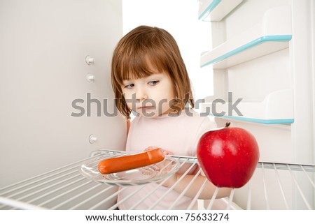 Girl looking inot an almost empty refrigerator seeing an apple and hot dog.