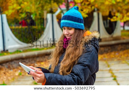 girl looking into a tablet with a smile on his face, located on the street in autumn day, in a green hat, the good news, work, business