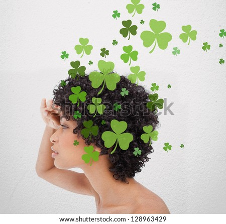 Girl looking into distance with shamrocks coming from her hair - stock photo