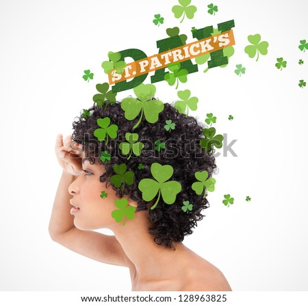 Girl looking into distance with shamrocks coming from her hair and st patricks day greeting - stock photo
