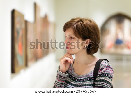 Girl looking pictures in art  gallery - stock photo