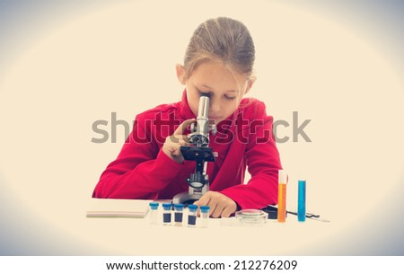 girl looking through a microscope - stock photo
