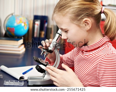 Girl looking through a microscope at home learning table - stock photo
