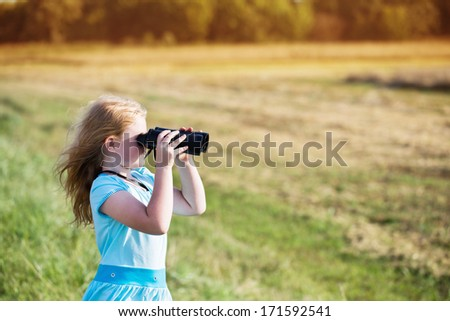 girl looking through binoculars outdoor - stock photo
