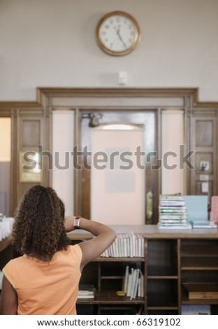 Girl looking through books at library